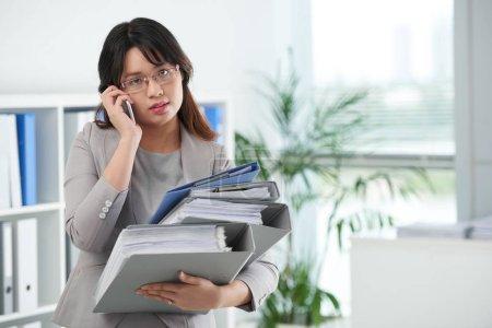 Female entrepreneur with many folders