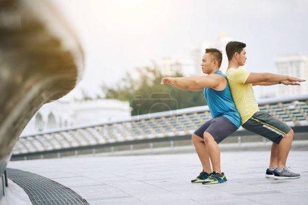 sportsmen doing squats back to back