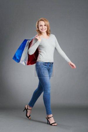 Photo pour Heureuse cliente marchant avec des sacs à provisions - image libre de droit