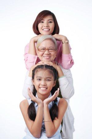 Foto de Feliz tres generaciones de mujeres sonriendo a cámara - Imagen libre de derechos