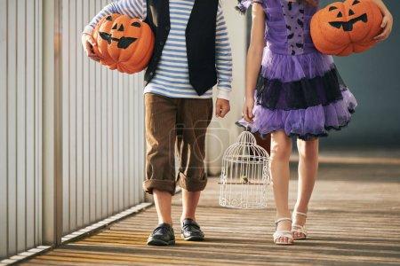 Photo pour Cropped image de deux enfants porteurs de décorations pour l'Halloween - image libre de droit