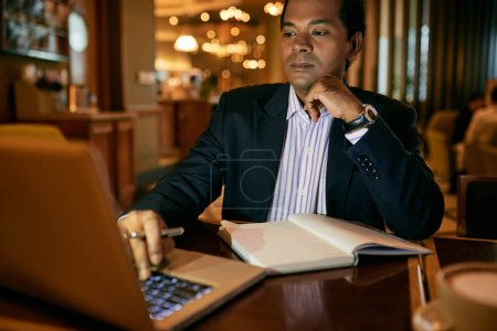 Businessman working on laptop and taking notes