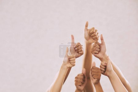 Photo for Hands of many people showing thumbs up, on beige background - Royalty Free Image