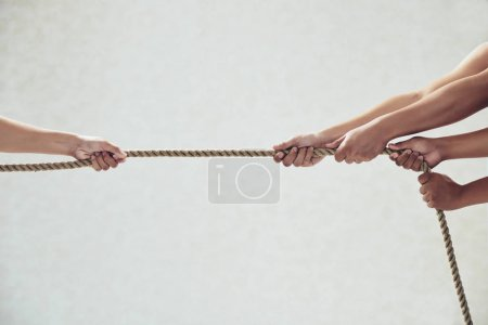 Hands of rivals pulling tug of war