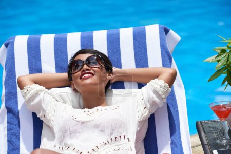 woman enjoying sunbathing by pool