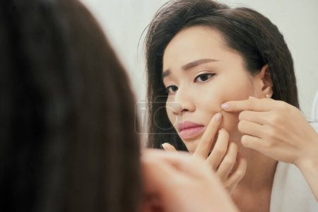Photo for Young woman squeezing out pimple on her check - Royalty Free Image