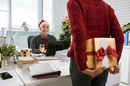 Business lady hiding present for chief