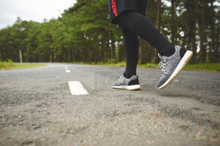 Jogger ready to run along road