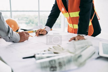 Engineers working on new building blueprint