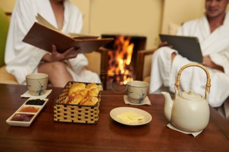 Photo for Cropped image of couple in bath robes having breakfast at fireplace - Royalty Free Image