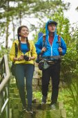 cheerful couple hiking in forest