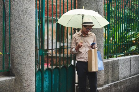 man with umbrella checking smartphone