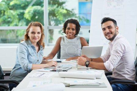 Photo pour Bonne équipe d'affaires souriante à la table de réunion - image libre de droit