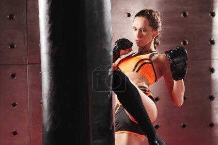 Woman kicking punching bag