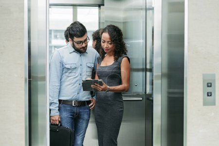 Business people standing in elevator and discussin...