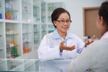 Pharmacist talking to drugstore customer
