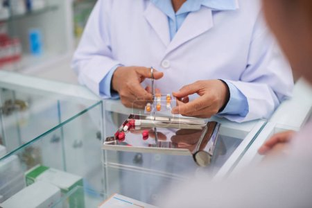 Pharmacist cutting package of pills