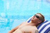Man sunbathing near swimming pool
