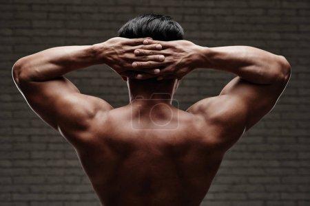 muscular man holding hands behind  head