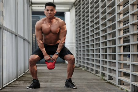 Sportsman doing squats with kettlebell