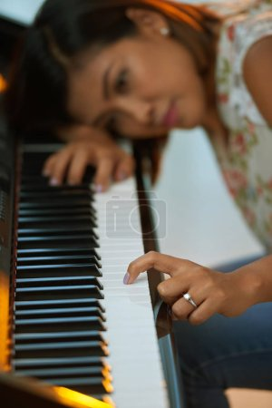 Woman pushing piano key