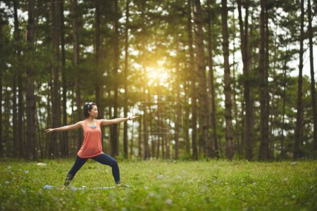 Photo for Pretty Asian woman practicing yoga in forest - Royalty Free Image