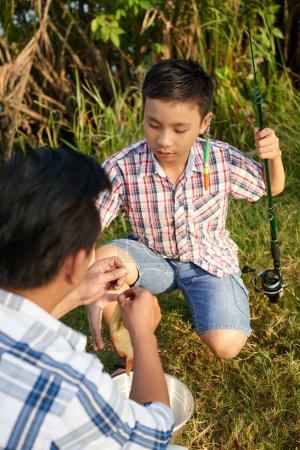 man helping to boy with fishing tackle