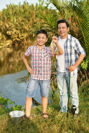 man and boy standing with fish