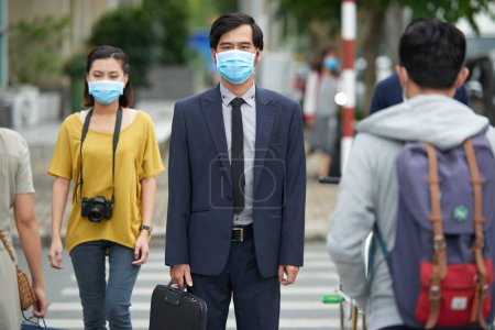 Photo for Asian businessman in protective mask looking at camera seriously while standing against pedestrian crossing - Royalty Free Image