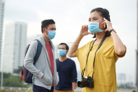 Woman putting on protective mask