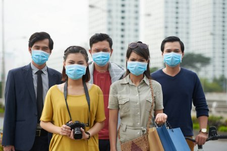 Photo for Asian people looking at camera with dissatisfied face expressions while suffering from air pollution in city center - Royalty Free Image