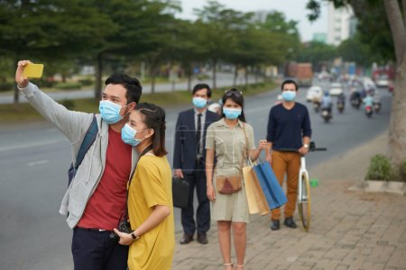 couple in protective masks taking selfie