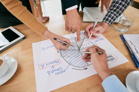 Photo pour Mains des gens d'affaires pointant au diagramme de cercle - image libre de droit