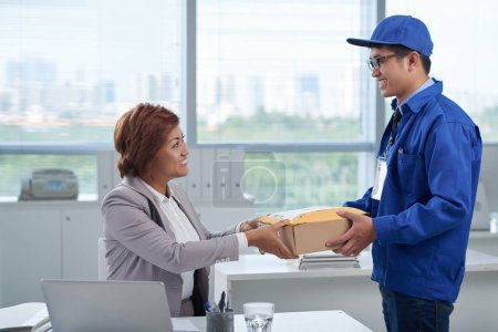 Photo for Business woman receiving package from delivery man - Royalty Free Image