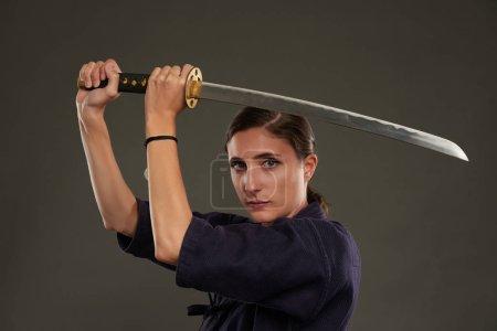 Photo pour Belle femme levant épée katana et regardant la caméra - image libre de droit