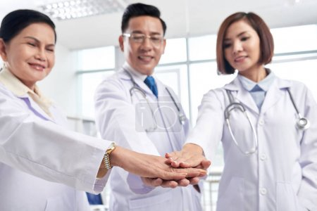 asian Doctors stacking hands to support each other before day of work