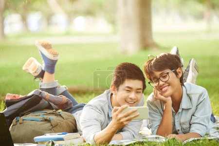 Smiling Asian friends watching funny video on smartphone while relaxing on green lawn in public park, blurred background