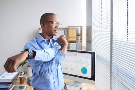 Smiling Black business executive stretching his arms during little break
