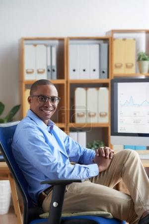 Portrait of happy business executive sitting on his office armchair