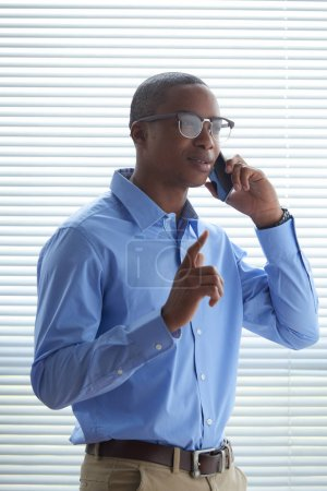 Portrait of Black young business executive talking on the phone with coworker