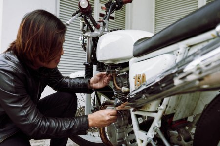 Profile view of mechanic man wearing leather jacket and servicing vintage motorcycle