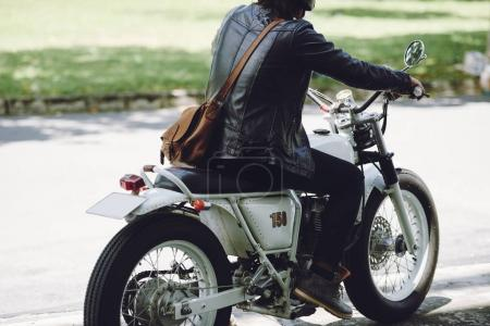 Back view of man wearing leather jacket and riding vintage motorcycle on road