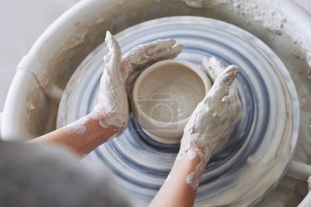 Close-up image of woman working on clay pot