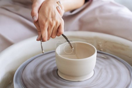 Hands of potter using wire cutter to shape the pot