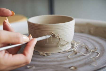 Female potter carving clay bowl with special tool