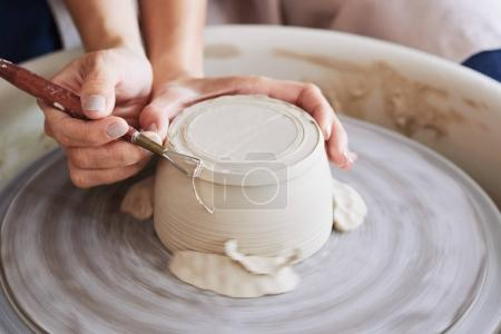 Potter using trim tool to get rid of excess clay