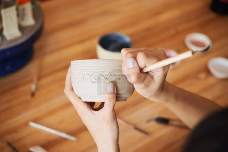 Master carving vegetative ornament on a pot