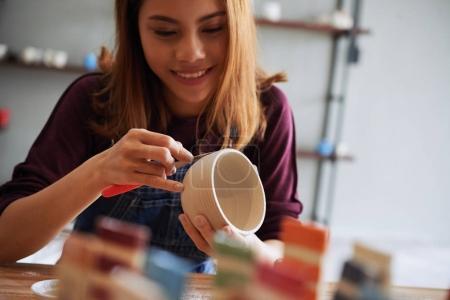 Young Asian woman enjoying pottery process in studio