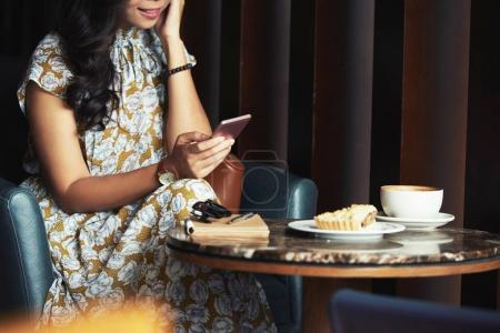 Cropped image of woman texting to friends when having coffee and dessert in cafe
