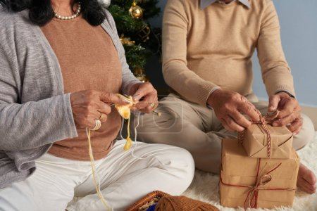 Grandfather packing presents and grandmother knitting for Christmas